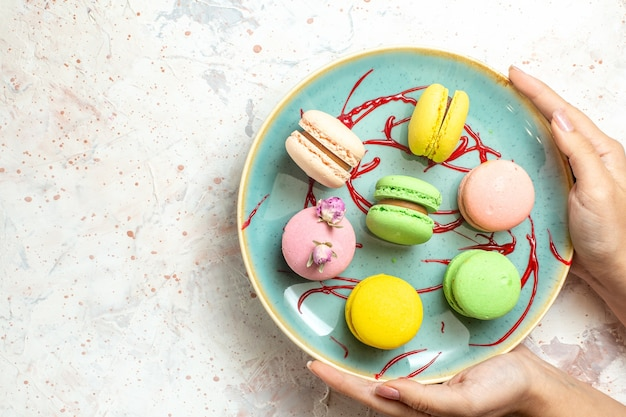 Top view yummy french macarons inside plate on white cake biscuit sweet