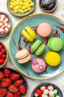 Vista dall'alto deliziosi macarons francesi con frutti di bosco e caramelle su biscotto dolce torta bianca