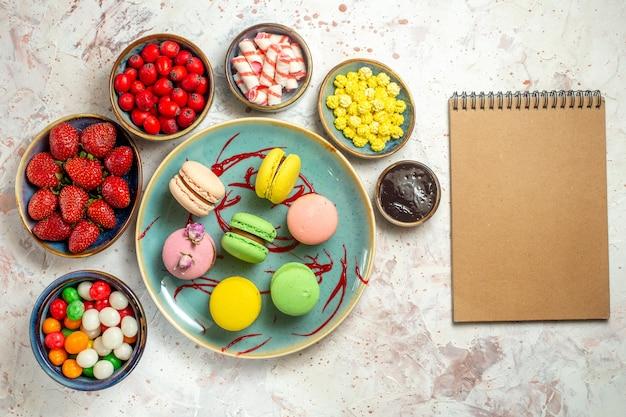 Vista dall'alto deliziosi macarons francesi con frutti di bosco e caramelle su biscotto dolce con torta da scrivania bianca