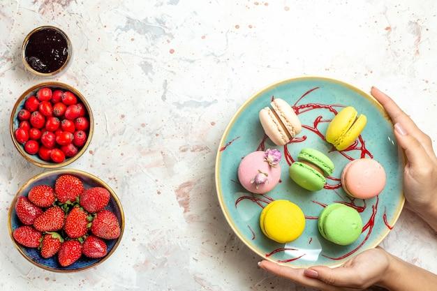 Вид сверху вкусные французские макароны с ягодами на белом пироге, бисквитном сладком