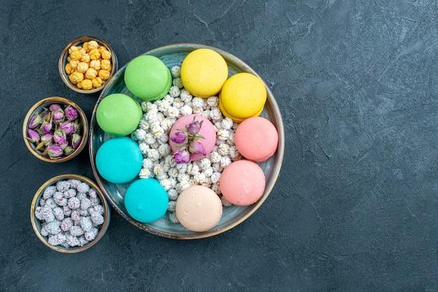Vista dall'alto gustosi macarons francesi con caramelle su grigio