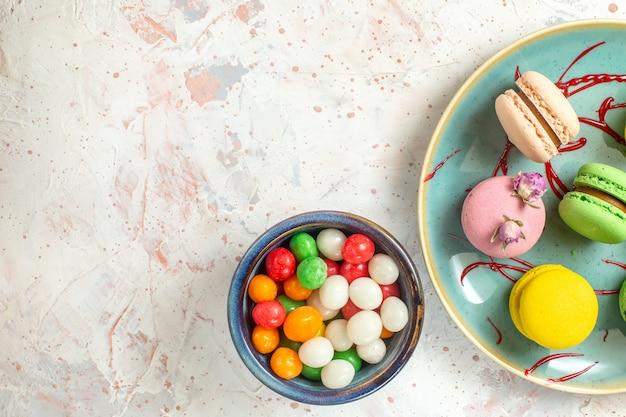 Vista dall'alto deliziosi macarons francesi con caramelle su biscotto dolce bianco chiaro