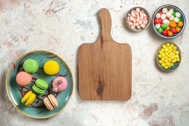 Vista dall'alto deliziosi macarons francesi con caramelle su biscotto con torta bianca