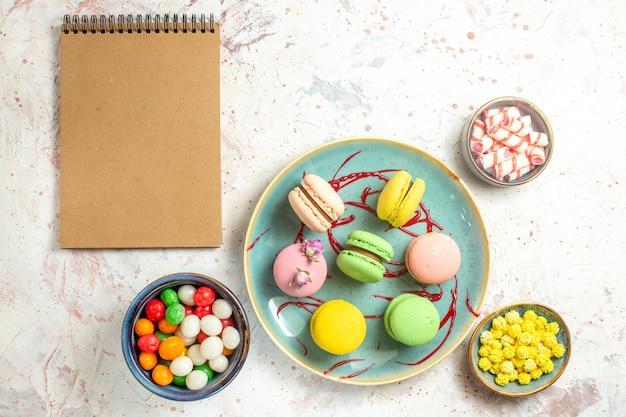 Vista dall'alto deliziosi macarons francesi con caramelle su biscotto dolce bianco