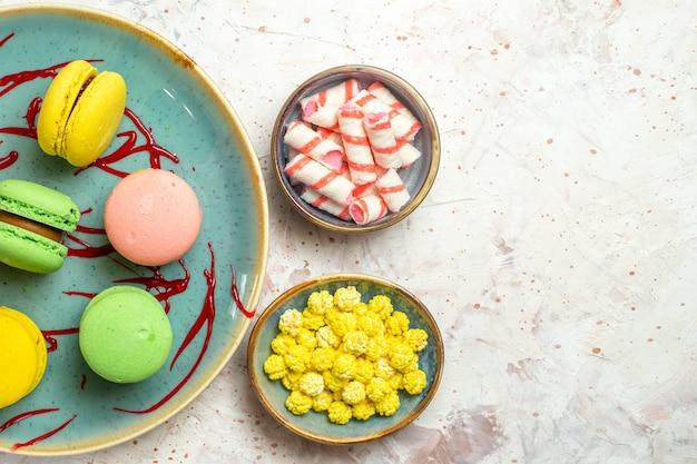 Vista dall'alto gustosi macarons francesi con caramelle su biscotti dolci bianchi