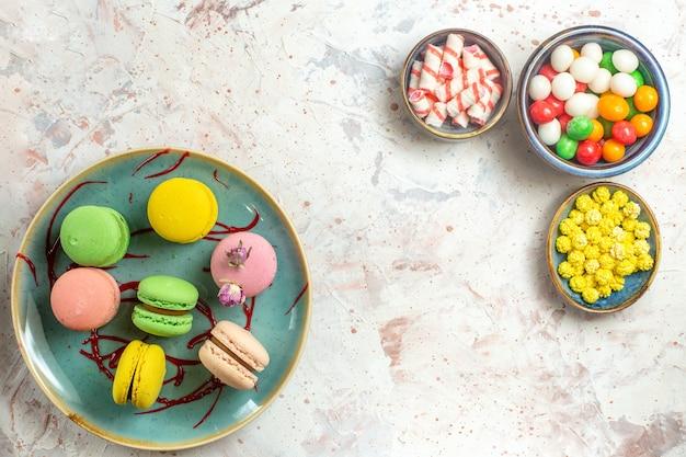 Vista dall'alto deliziosi macarons francesi con diverse caramelle su biscotto con torta bianca