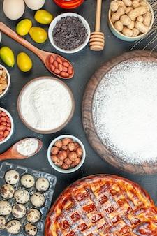 トップビューダークデザートパイにジャムナットと小麦粉を添えたおいしいフルーツパイスウィートティーケーキ生地焼き砂糖