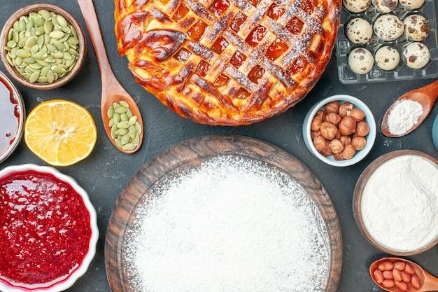 トップビューダークデザートパイにジャムナッツと小麦粉を添えたおいしいフルーツパイスウィートティーケーキ生地ビスケット焼き砂糖