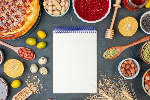濃い色の生地のナッツの写真ケーキレーズンビスケットパイデザートにメモ帳とナッツが付いた上面図おいしいフルーツパイ