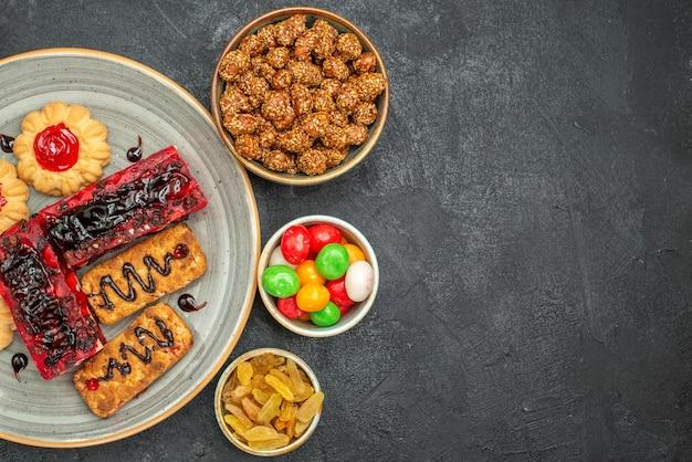 Vista dall'alto di deliziose torte fruttate con biscotti e caramelle al buio