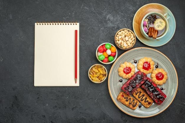 Vista dall'alto di deliziose torte fruttate con biscotti e tazza di tè al buio