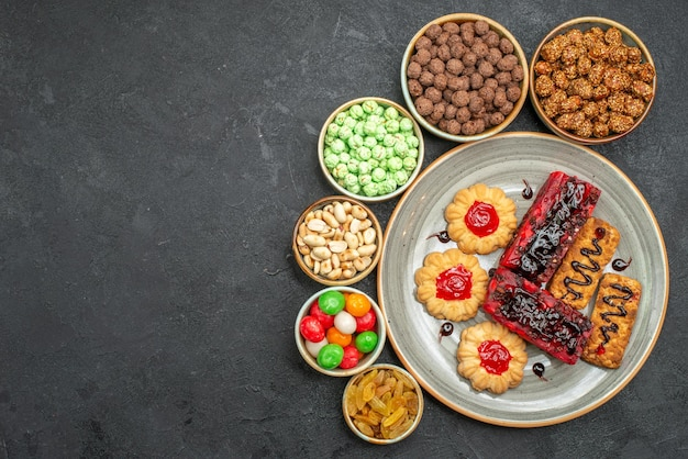 Top view of yummy fruity cakes with nuts and candies on grey