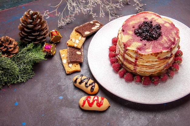 Top view of yummy fruity pancakes with jelly and strawberries on dark table