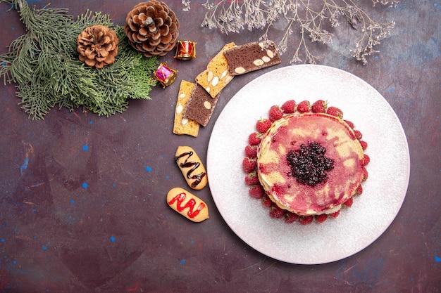 Vista dall'alto di gustosi pancake fruttati con gelatina e fragole al buio