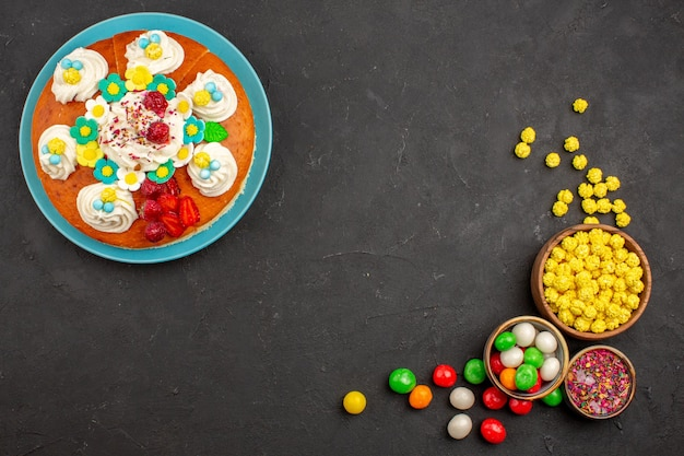 Top view of yummy fruity pie with candies on dark