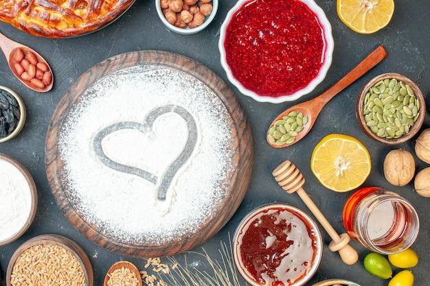 トップビューダークフルーツの甘いパイシュガーティーペストリービスケットケーキに小麦粉ジャムとナッツを添えたおいしいフルーティーパイ