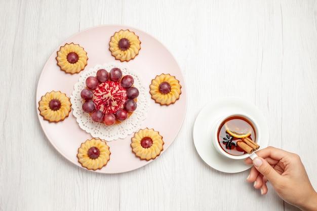 上面図白いテーブルデザートビスケットパイクッキーにお茶とおいしいブドウのケーキ