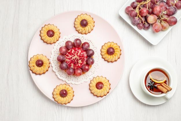 Vista dall'alto deliziose torte di uva con la tazza di tè sul biscotto torta biscotto dessert tavolo bianco