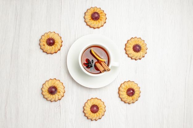上面図白いテーブルの上にお茶、甘いデザートビスケットパイとおいしいブドウのクッキー