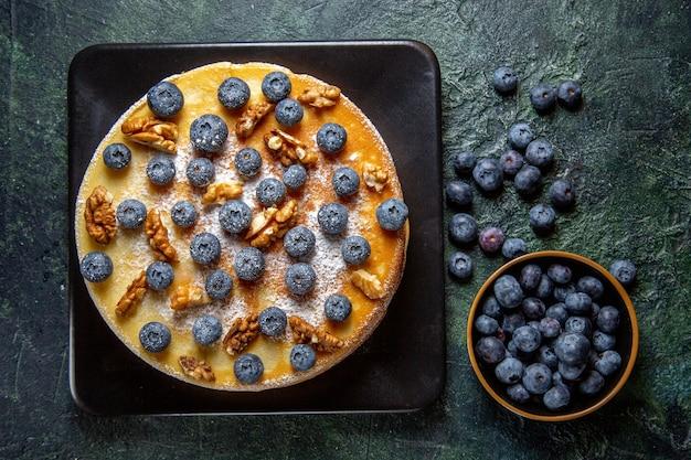プレートの暗い表面の中にブルーベリーとクルミが入った上面図おいしいハニーケーキ
