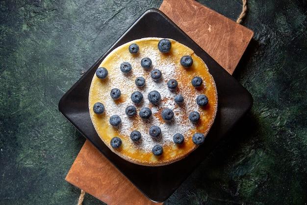 プレートの暗い表面の中にブルーベリーが入った上面図おいしいハニーケーキ