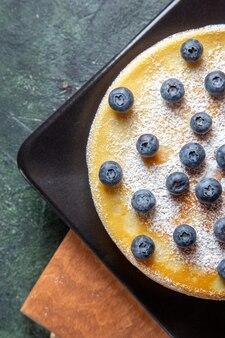 플레이트 어두운 표면 안에 블루 베리와 상위 뷰 맛있는 꿀 케이크