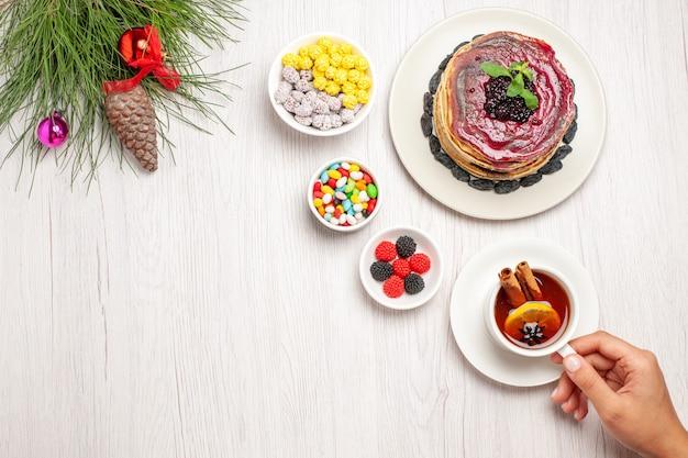 사탕과 흰색 차 한잔과 함께 상위 뷰 맛있는 젤리 팬케이크