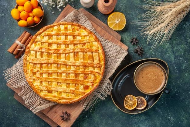 Top view of yummy kumquat pie on dark surface