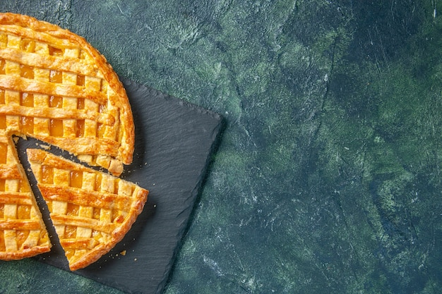 Top view of yummy kumquat pie with sliced one piece on dark surface