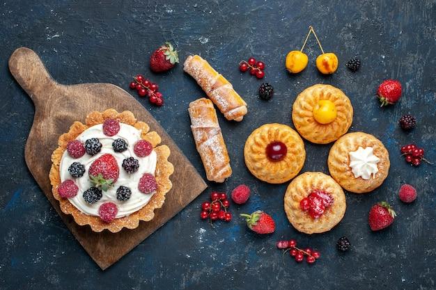 Вид сверху вкусный маленький торт со сливками и ягодами вместе с печеньем-браслетами на темном столе, ягодный фруктовый торт, бисквитная выпечка