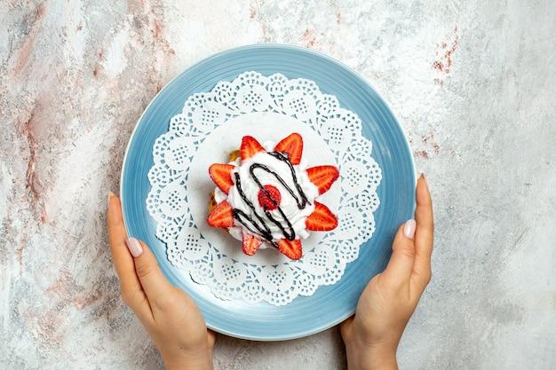 Вид сверху вкусный маленький торт со сливками и клубникой на белом