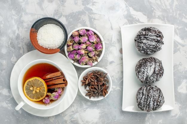 Vista dall'alto deliziose torte torte al cioccolato con tazza di tè su sfondo bianco