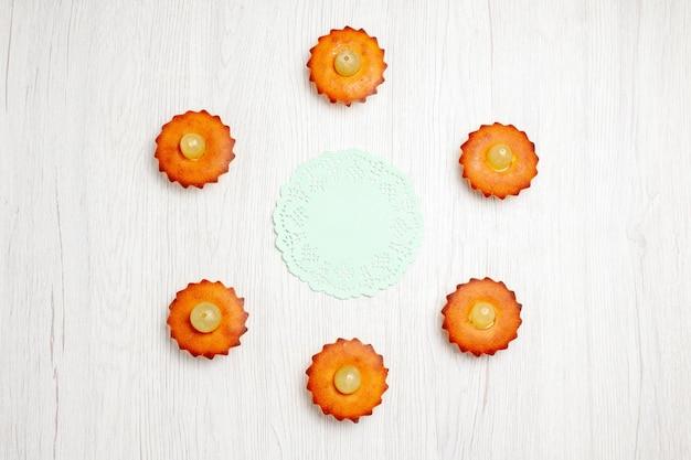 Vista dall'alto deliziose piccole torte allineate su una scrivania bianca biscotto da dessert torta da tè torta biscotto dolce
