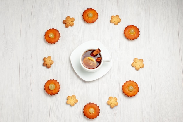 Top view yummy little cakes lined with cookies and cup of tea on white surface dessert biscuit tea cake pie cookie
