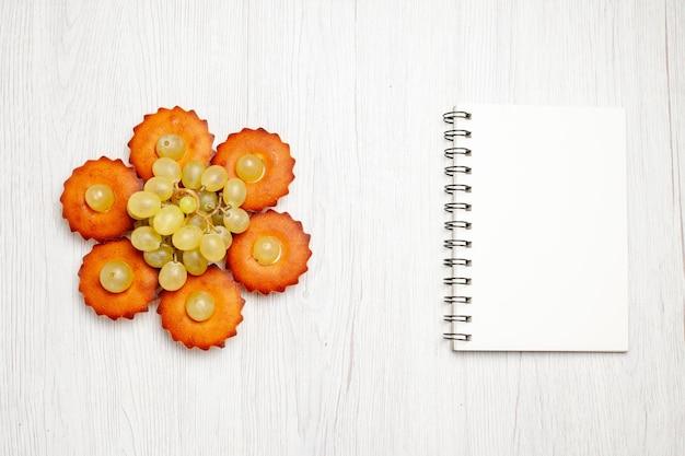 上面図白い机の上のブドウが並ぶおいしい小さなケーキケーキパイ甘いデザートティークッキー