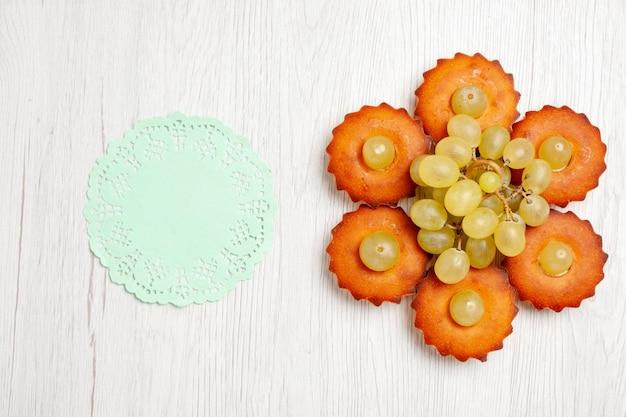 上面図白い机の上にブドウが並ぶおいしい小さなケーキティーケーキパイ甘いデザートクッキー