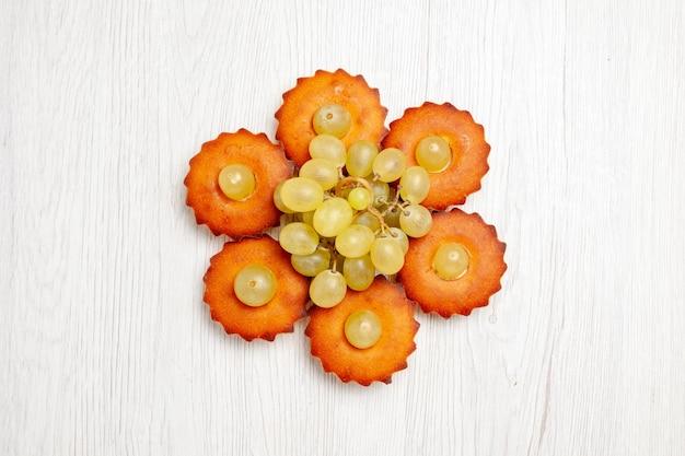 Vista dall'alto deliziose piccole torte dolci perfetti per il tè allineati con l'uva su una torta da scrivania bianca torta dolce da dessert biscotti da tè
