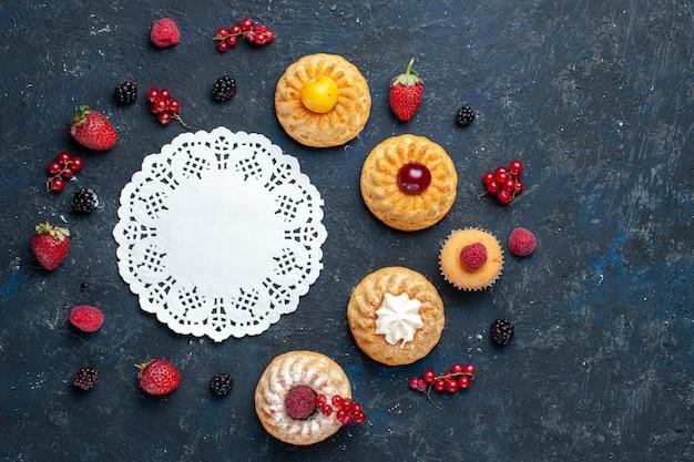 Вид сверху вкусные маленькие пирожные с ягодами фрукты на темном фоне ягодный фруктовый торт бисквитная выпечка