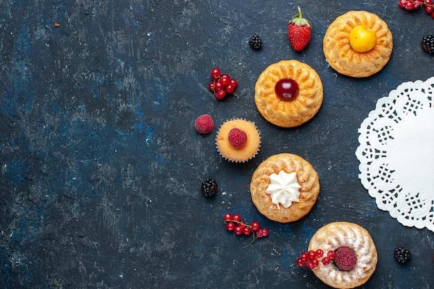 Вид сверху вкусные маленькие пирожные с ягодами фруктами на темном фоне ягодный фруктовый торт бисквит