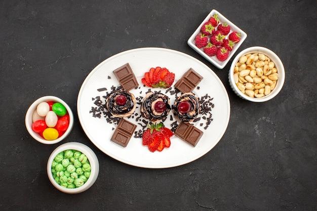 Vista dall'alto deliziose torte con barrette di cioccolato, caramelle e noci su una superficie scura, torta di frutta alle noci, biscotto a base di bacche