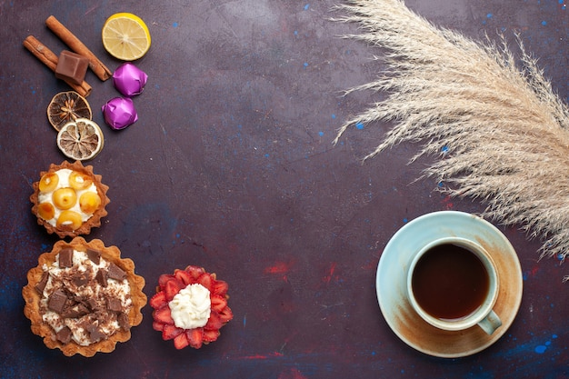 Vista dall'alto di deliziose torte con crema insieme a caramelle e tè sulla superficie scura