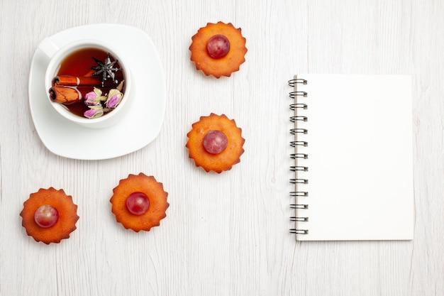 上面図白い表面にお茶を入れたおいしい小さなケーキデザートクッキービスケットティーケーキパイ 無料写真