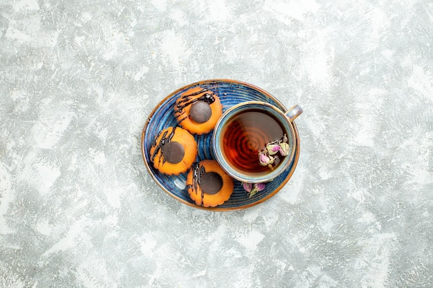 Vista dall'alto deliziose piccole torte con una tazza di tè sulla superficie bianca torta biscotto biscotto dessert tè dolce