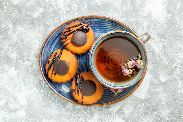 Top view yummy little cakes with cup of tea on white surface cake biscuit cookie dessert tea sweet