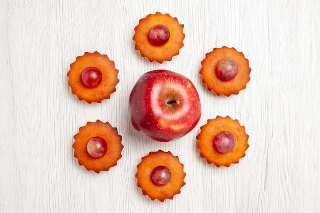 上面図白い表面に新鮮なリンゴとおいしい小さなケーキデザートビスケットティーケーキパイクッキー