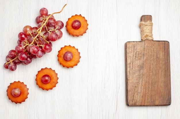 Вид сверху вкусные маленькие пирожные со свежим виноградом на белой поверхности фруктовый чай десертное печенье бисквитный торт пирог
