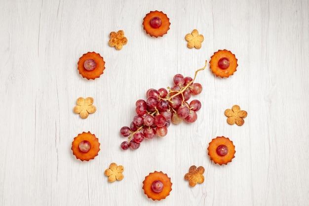 上面図白い表面にブドウとクッキーが付いたおいしい小さなケーキフルーツティーデザートクッキービスケットケーキパイ