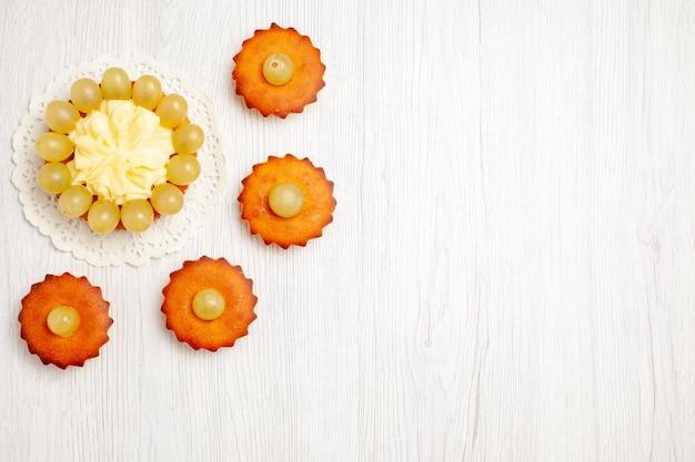 上面図白い表面に緑のブドウとおいしい小さなケーキフルーツティーデザートクッキービスケットケーキパイ