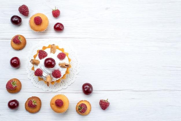 Вид сверху вкусные маленькие пирожные с малиной вместе с печеньем и пирожными на светлом столе торт бисквит сладкие ягоды запекать фрукты