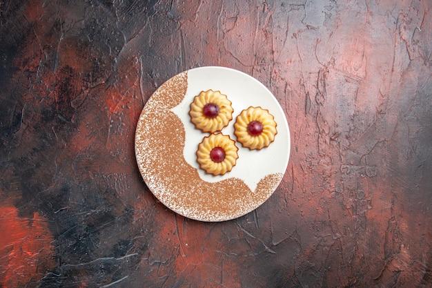 Вид сверху вкусного печенья внутри тарелки на темном столе, сладкий бисквитный торт
